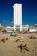 Israel, Tel Aviv, people on the sand sunbathing