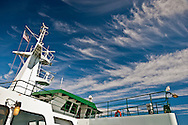 Cirrus clouds punctuate the sky with the mast and bridge of a Washington State Ferry as it crosses Puget Sound, WA.