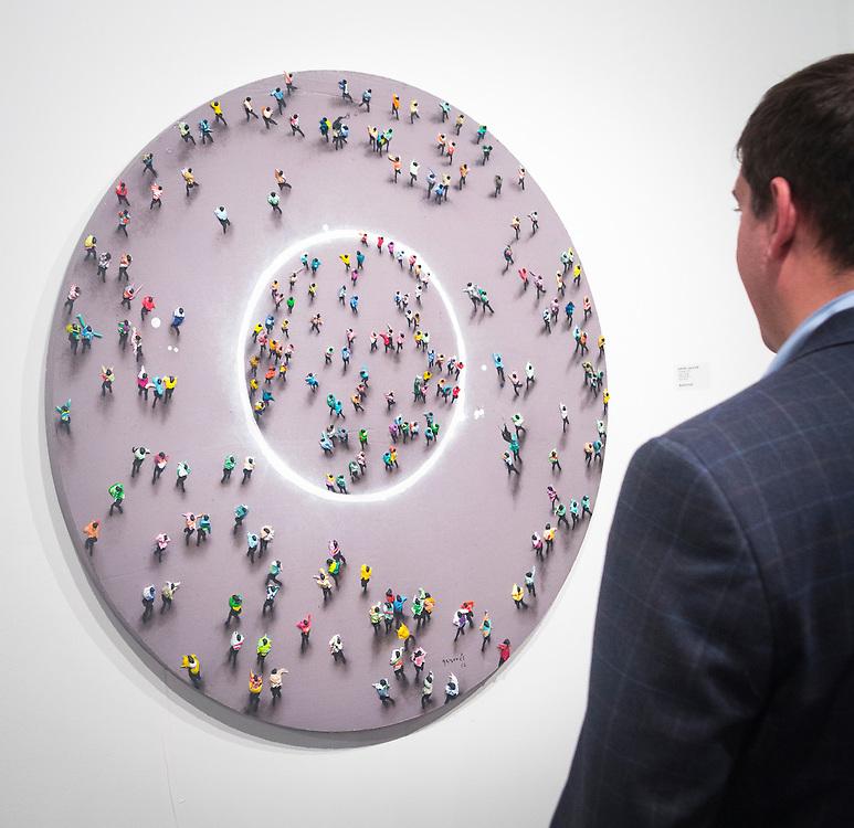 Man studies Concéntrico by Juan Genovés at Art Basel Miami 2012.