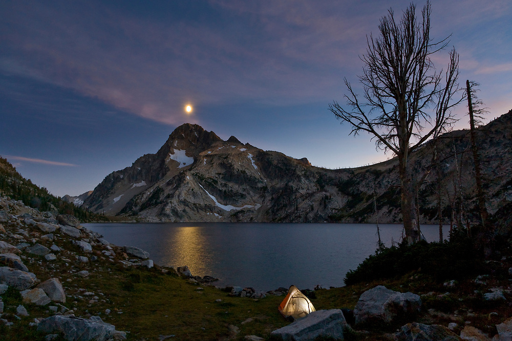 Night shot at Sawtooth Lake with a half moon glowing and Mt. Regan at 10,190 ft. / 3106 meters features warmth of tent light in the foreground.  Licensing and Open Edition Prints.