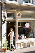 Young woman shopping Beadies in chic ladies fashion shop in Huidenstraat in the Nine Streets shopping district, Amsterdam