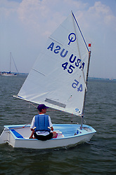 Stock photo of a boy guiding his sailboat on the water