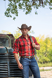 hot masculine cowboy leaning against an old truck