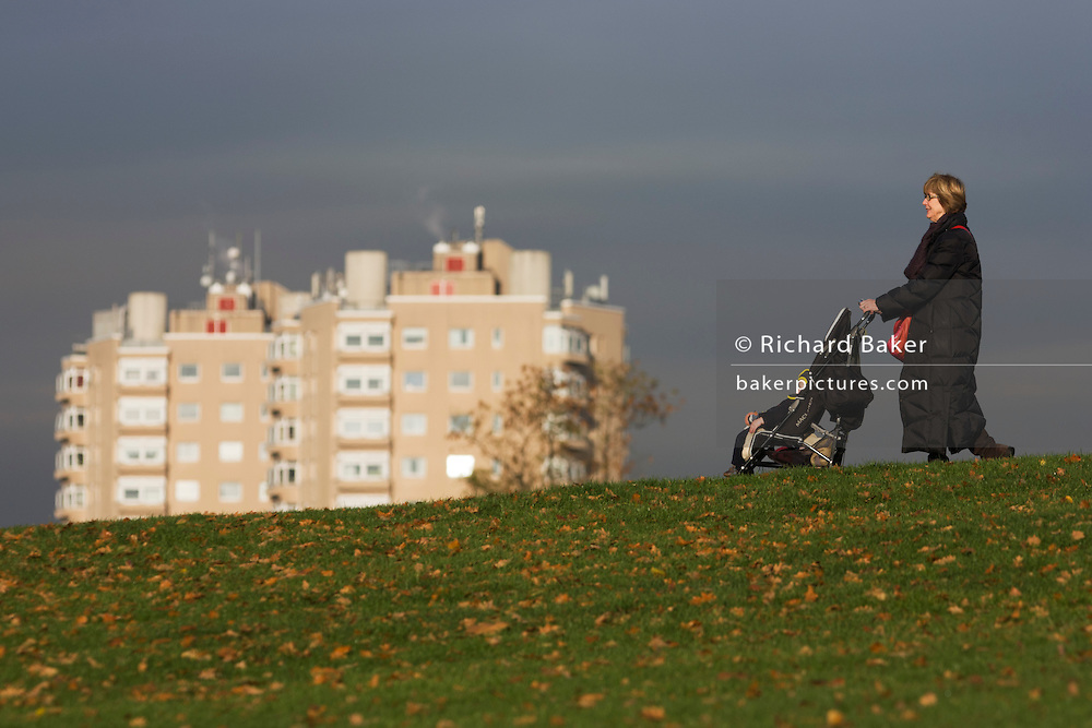 Grandmother and child on bike with high-rise flats seen from Brockwell Park, Herne Hill, South London.