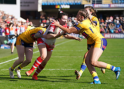 St Helens' Leah Burke (centre) tackled by Leeds Rhinos' Sophie Nuttall, Caitlin Beevers and Elle Frain during the Betfred Women's Super League Grand Final at Emerald Headingley Stadium, Leeds Picture date: Sunday October 10, 2021.