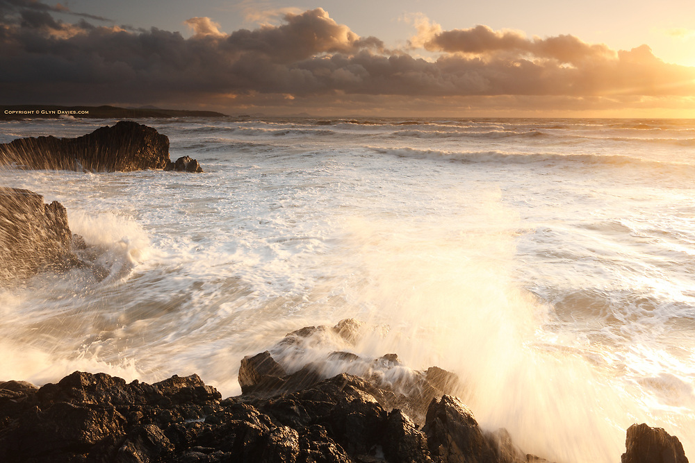 Powerful storm surf at sunset in winter gales coming from the Irish Sea at Porth Tyn Tywyn near Rhosneigr on the West Coast of Anglesey.
