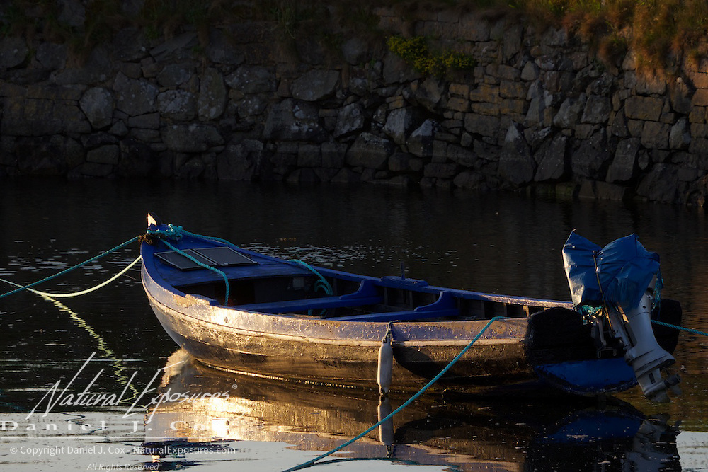 Early morning light bathes a small fishing boat in the harbor of Galway, Ireland.