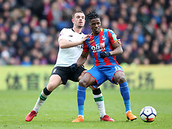 Crystal Palace's Wilfried Zaha (right) and Liverpool's Jordan Henderson battle for the ball during the Premier League match at Selhurst Park, London.