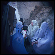 Afghan women wearing hijab and burqa sit together on an outing in the outskirts of Kabul.