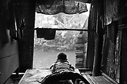 A boy relaxes and watches the rain from a house in the slum during the rainy season.