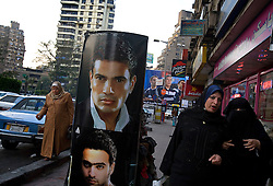 People are seen on the street in the wealthy neighborhood of Mohandessin in Cairo, Egypt, Dec. 21, 2005. Amr Khaled, the Islamic televangelist got his start here. Khaled, had previously been asked to leave Egypt as his revival gained strength. As a result he started preaching on several television shows, turning him into an international celebrity. Some religious scholars complain that Khaled has not been properly trained in Islam to command such a following.