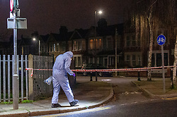 © Licensed to London News Pictures. 20/01/2020. London, UK. A forensic investigator searches for evidence on a footpath next to a park entrance. Police cordoned off a road & park and searched a property approximately half a mile from the location where an investigation was launched into the deaths of three men in Redbridge, all of whom had suffered apparent stab injuries.. Photo credit: Peter Manning/LNP