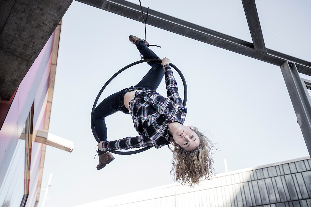 Beautiful female aerial dancer performing acrobatics on a ring in the city