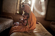 A mother is holding her malnourished child while sitting on their bed inside a feeding centre run by UNICEF in the town Shivpuri, Madhya Pradesh, India.