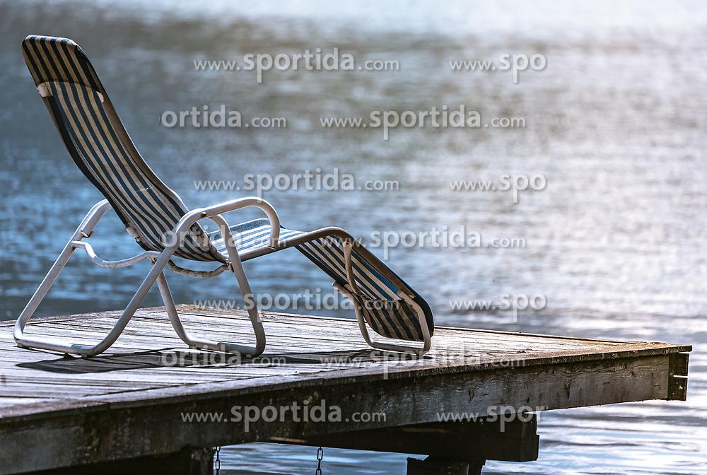 THEMENBILD - ein gestreifter Liegestuhl steht auf einem Steg am Ufer des Zeller Sees, aufgenommen am 20. April 2019, Zell am See, Österreich // a striped deckchair stands on a jetty on the shore of the Zeller lake on 2019/04/20, Zell am See, Austria. EXPA Pictures © 2019, PhotoCredit: EXPA/ Stefanie Oberhauser
