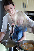 Polish mom helping daughter age 4 cook at stove. Zawady Central Poland