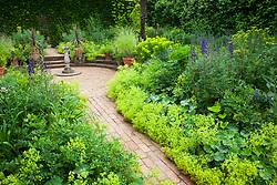 Alchemilla mollis, aconitums and euphorbia in Mrs Winthrop's Garden at Hidcote Manor. Lemon verbena and cordylines in terracotta pots