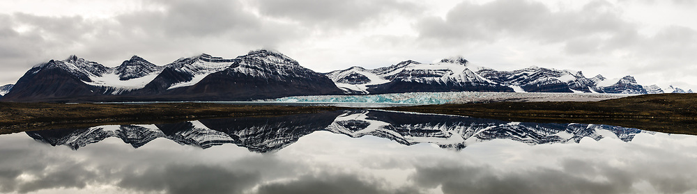 Sveabreen on Svalbard surrounded with mountains and their reflections.