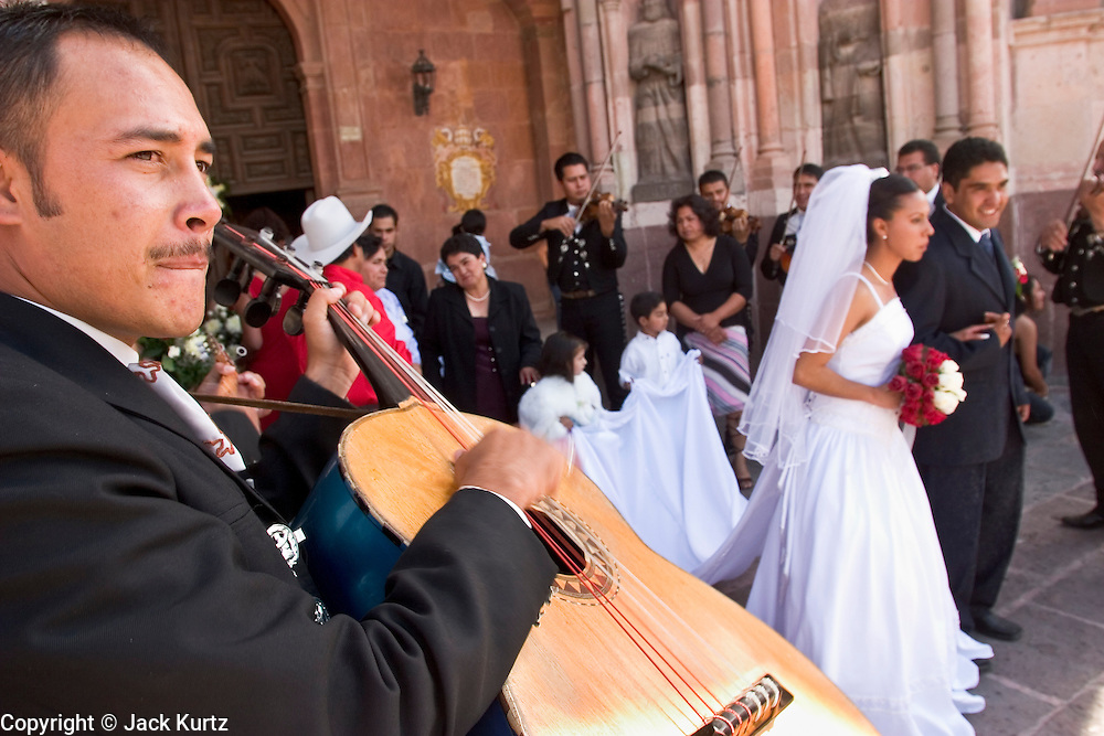 142302 MexTravel -- 03 APRIL 2004 - SAN MIGUEL DE ALLENDE, GUANAJUATO, MEXICO: Mariachis serenade newlyweds after their wedding at the Iglesia Parroguia, the principal Catholic church in San Miguel de Allende, Mexico. San Miguel, which was founded in the 1600s, is one of Mexico's premier colonial cities. It has very strict zoning and building codes meant to preserve the historic nature of the city center. About 7,500 US citizens, mostly retirees, live in San Miguel. PHOTO BY JACK KURTZ