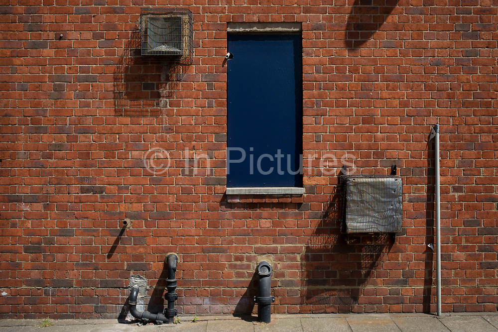 Doorway and various pipes servicing a building in London, England, United Kingdom.