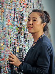 Artist Zhang Yanzi poses with one of her  works called 'wishing capsules' at the opening of her first ever UK exhibition, at Suregeon's Hall in Edinburgh. The piece is made up of thousands of capsules, each one filled with a handwritten wish by schoolchildren in China.<br /> <br /> (c) Dave Johnston / Eem