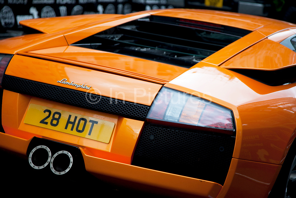 An orange Lamborghini super car with the number plate 28 HOT takes part in the Gumball Rally starting in London.