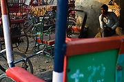 Homeless cycle rickshaw drivers smoke and relax at a tea stall in a parking lot next to the Yamuna River where they sleep. New Delhi, India.