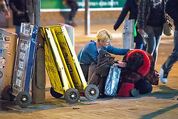 """© Licensed to London News Pictures . 15/12/2017. Manchester, UK. A woman tends to another who sits slumped over on the pavement in Piccadilly Gardens . Revellers out in Manchester City Centre overnight during """" Mad Friday """" , named for historically being one of the busiest nights of the year for the emergency services in the UK . Photo credit: Joel Goodman/LNP"""