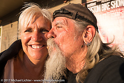 Cheryl and Mailman Kevin O'Brian on the porch of the Iron Horse Saloon during the annual Sturgis Black Hills Motorcycle Rally.  SD, USA. Monday August 7, 2017. Photography ©2017 Michael Lichter.
