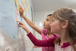 Schoolgirls studying a map of the world in classroom, Munich, Bavaria, Germany