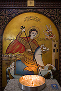 A St George and the Dragon's icon shrine with burning candles at St Tawdros (St Theodore's) Coptic Orthodox Christian Monastery, Luxor, Nile Valley, Egypt. The Copts are an ethno-religious group in North Africa and the Middle East, mainly in the area of modern Egypt, where they are the largest Christian denomination. Christianity was the religion of the vast majority of Egyptians from 400–800 A.D. and the majority after the Muslim conquest until the mid-10th century. Today, there are an extimated 9-15m Copts in Egypt.