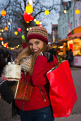 Portrait of young woman holding gift and shopping bag