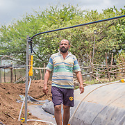 INDIVIDUAL(S) PHOTOGRAPHED: Prasad Tulpule. LOCATION: Ahirwade, Maharashtra, India. CAPTION: After filling his recently installed biogas unit with a mixture of fresh manure and water, Prasad walks the length of the drum to carry out a quick maintenance check. This simple technology ferments organic waste and turns it into methane gas, which Prasad's family is then able to use instead of firewood for cooking. Now that Prasad has access to a reliable and clean source of energy, he hopes to use his biogas-fuelled cookstove to develop medicinal products to sell at the nearby market. Sistema Biobolsa, a social enterprise supported by Shell Foundation, has installed more than 4,000 biogas units to date, helping families across the globe to access affordable and renewable energy.
