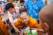 13 APRIL 2013 - BANGKOK, THAILAND: Thai novice monks receive alms during a merit making ceremony for Songkran at the Bangkok City Hall. Songkran is the traditional Thai New Year's Festival. It is held April 13-16. Many Thais mark the holiday by going to temples and making merit by giving extra alms to monks or offering extra prayers. They also mark Songkran with joyous water fights. Songkran has been a national holiday since 1940, when Thailand moved the first day of the year to January 1.    PHOTO BY JACK KURTZ