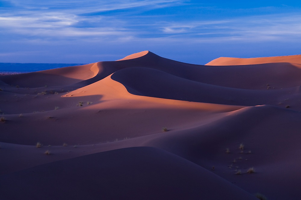 Last light falls on the large sand dunes of Erg Zehar, a three-day camel trek away from the outpost town of M'hamid, Morocco.