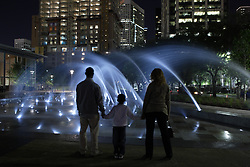 Stock photo of a family of three standing in front of the Lighted Fountains at night in Discovery Green Park