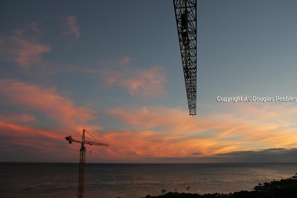 Construction cranes at sunset