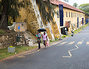 Family walking with umbrella for shade fort doorway historic town of Galle, Sri Lanka, Asia