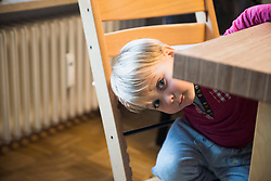 Little boy curiously looking from under the edge of the table, Munich, Germany