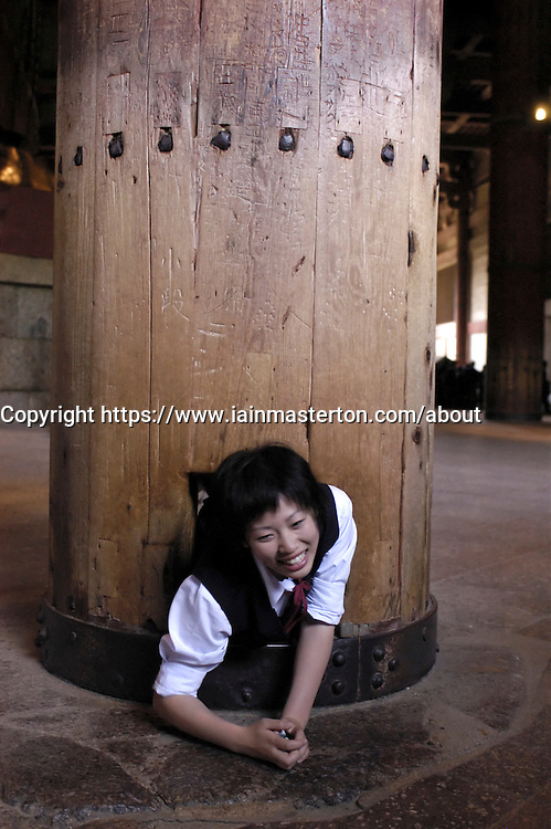 Young girl squeezing through hole in wooden column at Todaiji Temple in Nara Japan