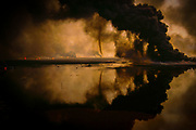 KUW_024_xs<br /> Kuwait.. Tornados of smoke reflected in an oil lake in the Al Burgan field after the first Bush War, the Gulf War.