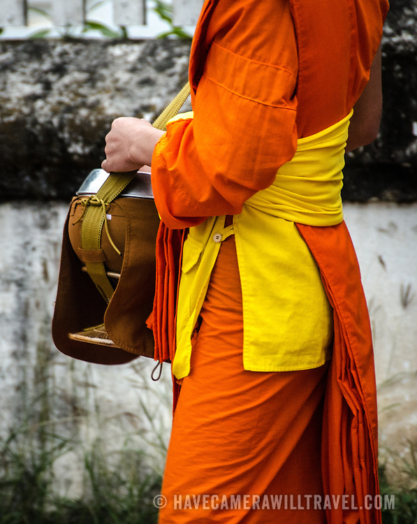 A novice in his bright saffron robe walks past locals and tourists offering food in an early morning ritual known as tak bat.