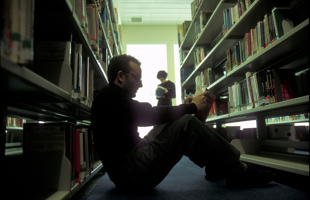 Male student studying in university library,