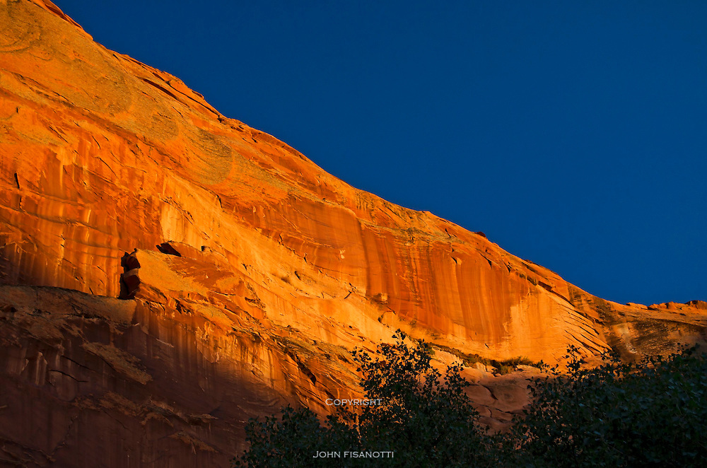 The last of the day's sunlight illuminates high up on the sandstone wall