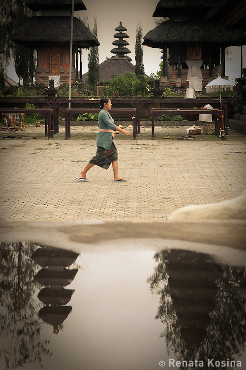 A Balinese woman walks through Ulun Danur Batur temple. Named after a goddess that rules the water supply, this pura is the second most significant  in Bali and has over 100 shrines overlooking Gugung Batur mountain and Lake Batur bellow.