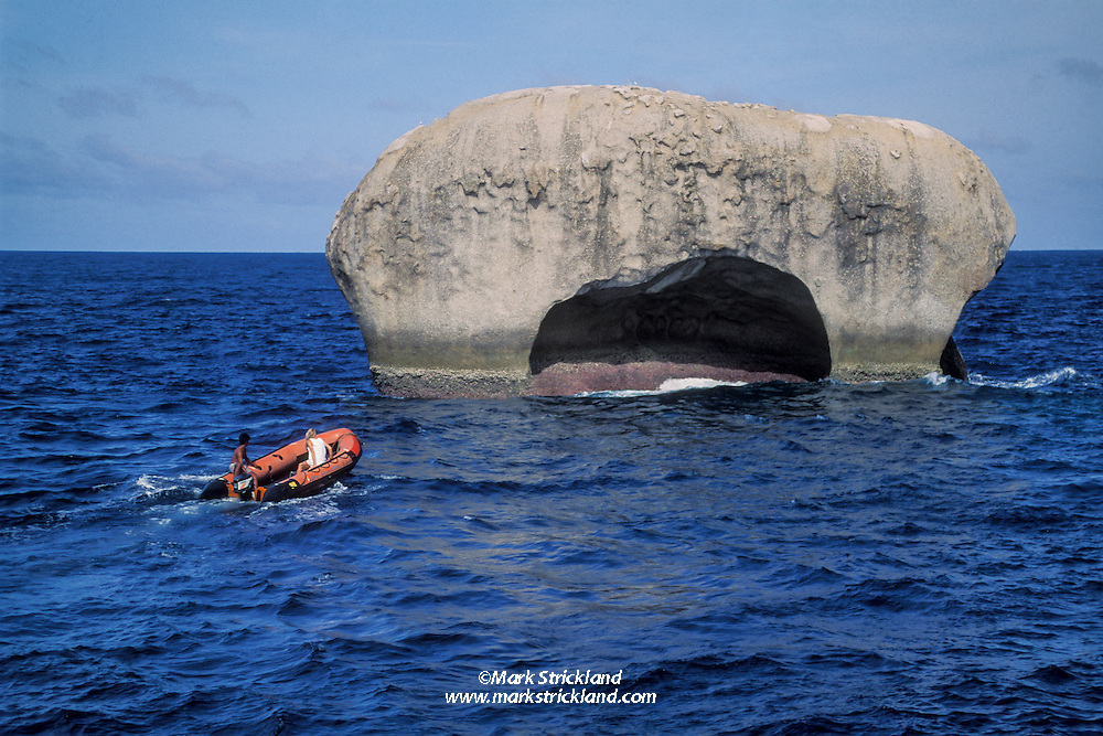 A couple in a dinghy approach an iconic granite rock pinnacle at a site called Elephant's Head, Similan Islands Marine National Park, Thailand, Andaman Sea
