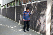 A middle aged man checks his mobile phone on 24th May 2017 in London, United Kingdom.  From the series Our Small World, an observation of our mobile phone obsessions