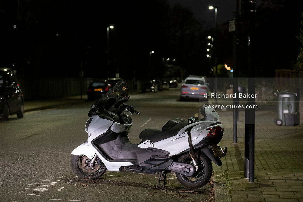 A Suzuki Burgman scooter is locked to a lamp post in a residential street in south London, on 21st January 2021, in London, England.