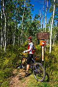 Mountain biker and trail sign on the Galloping Goose Trail, Uncompahgre National Forest, Colorado USA (MR)