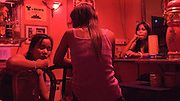 SEX INDUSTRY TOURISM. South East Asia, Cambodia, Phnom Penh. Taxi girls, prostitutes, serve foriegn tourists & Khmer, Cambodians. The sex industry is part of the fabric, servicing all classes of Cambodian society. Girls are forced into prostitution because of poverty and corruption that exists across the country. People might earn 1 to 2 $ per day, even less in rural areas, so the lure of prostitution is high. Families can sell young girls, virgins, for several hundred dollars. Cheap brothels line the streets in parts of the city centre, near railway tracks, and on the periphery. Sex for Cambodians at cheap prices in the street brothels, as low as 1 $ US, to exorbitant fees in penthouse hotel suites for the rich. Sex tourism industry attracts Western and Asian tourists typically paying 10 - 30 $ US. Expressions such as 'yam yam', eating, for a blowjob 'bam bam' for intercourse. There are 'lady-boys', youths, who use the money to pay for  sex change operations. Prostitutes spend lots of money on make-up, clothes, and mobile telephones. They live in squalor. Due to public advertising campaigns and outreach work, Aids and HIV cases have dramatically decreased, in Cambodia, since the late '90s. Condoms are encouraged, are cheap and widely available. This is seen as  a success story by medical and health authorities. There are risks as ex-prostitutes known as 'sweethearts' don't use condoms with their partners. Brothels, v & madams take their cut, but many taxi-girls work as free agents. Bars, pool halls or beer gardens have staff and taxi-girls available to service male clients, some work as barmaids or escorts. There is violence against prostitutes; gang-rape and murder by Khmer gangs. Once a girl has worked as a prostitute it is unlikely she can ever marry.///Young underage girls working as escorts and bar staff in a girls bar.